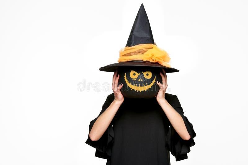 Ung kvinna i häxor hatt och hållande pumpa för dräkt som är främst av hennes framsida Allhelgonaaftonhäxa med den läskiga lyktan  arkivbilder