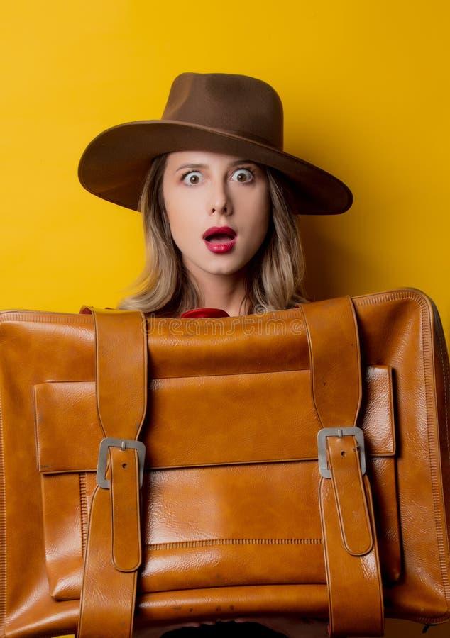 Ung kvinna i hatt med resväskan royaltyfria foton