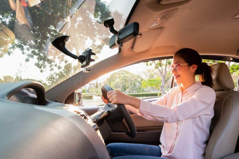 Ung kvinna i hennes bil, medan köra en bil som kör bilbegrepp royaltyfri bild