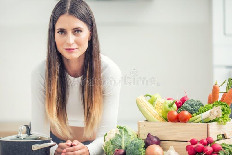 Ung kvinna i hennes kök med den nya organiska grönsaken som ser in i kameran arkivfoto