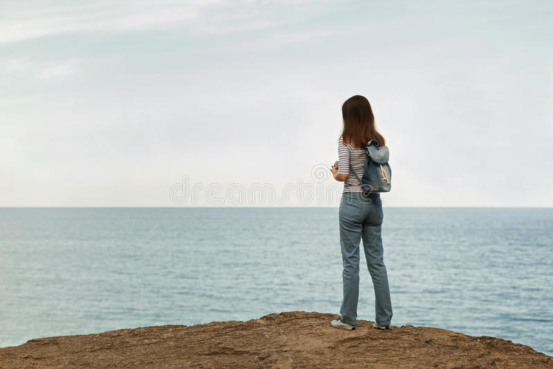 Ung kvinna i jeans, i randig överkant och gymnastikskor på stranden b arkivbild