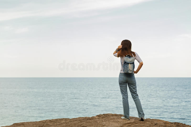 Ung kvinna i jeans, i randig överkant och gymnastikskor på stranden b royaltyfri fotografi