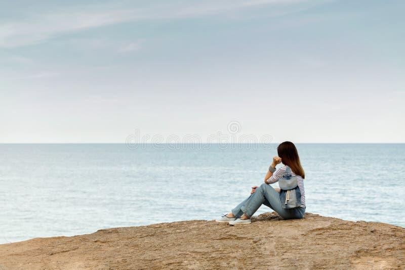 Ung kvinna i jeans, i randig överkant och gymnastikskor på stranden b fotografering för bildbyråer