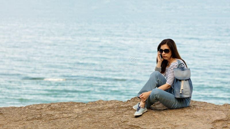 Ung kvinna i jeans, i randig överkant och gymnastikskor på stranden b royaltyfria foton