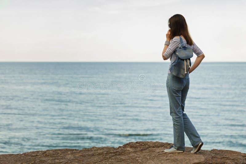 Ung kvinna i jeans, i randig överkant och gymnastikskor på stranden b arkivfoto