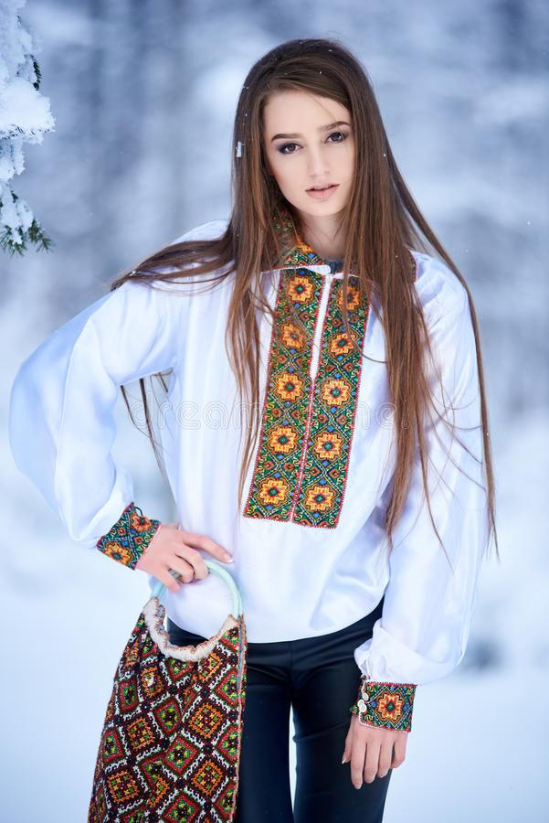 Ung kvinna i jeans och den vita traditionella broderade blusen med linnepåsen på vinterbakgrund royaltyfri bild