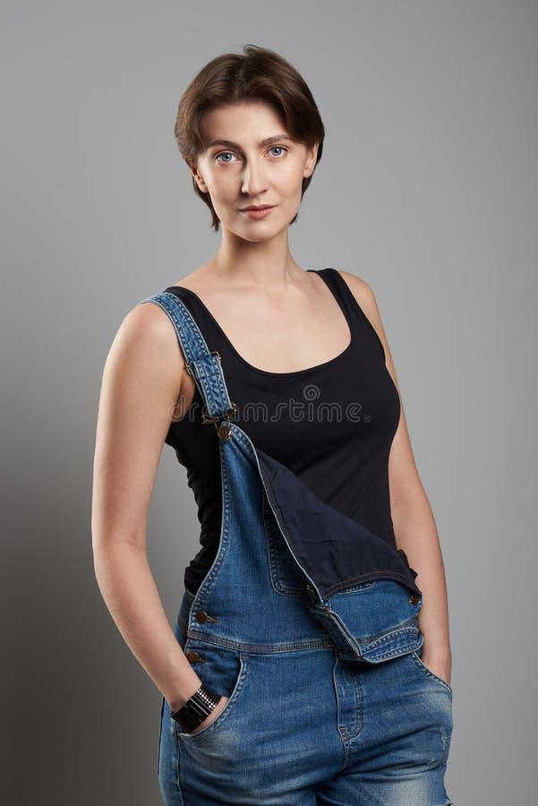 Ung kvinna i jeansoveraller arkivfoton