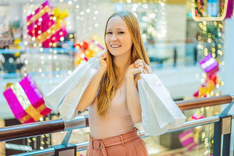 Ung kvinna i julgalleria med julshopping Skönhetbu arkivfoton