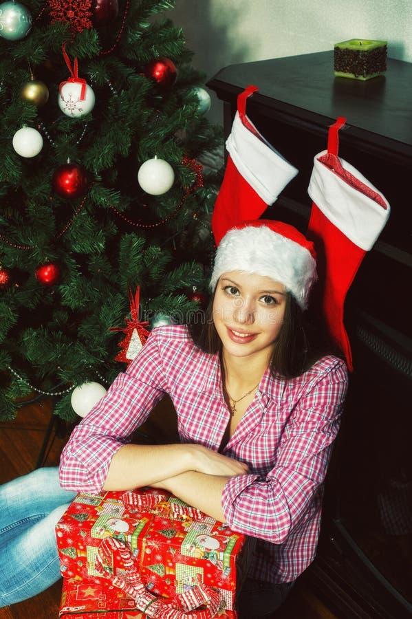 Ung kvinna i jultomtenhatt på jul arkivbild
