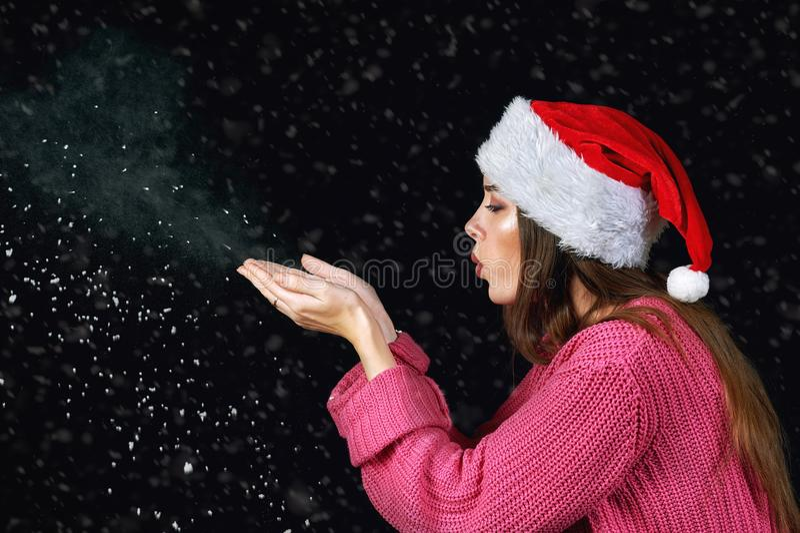 Ung kvinna i jultomtenhatten som spelar med snö royaltyfri foto