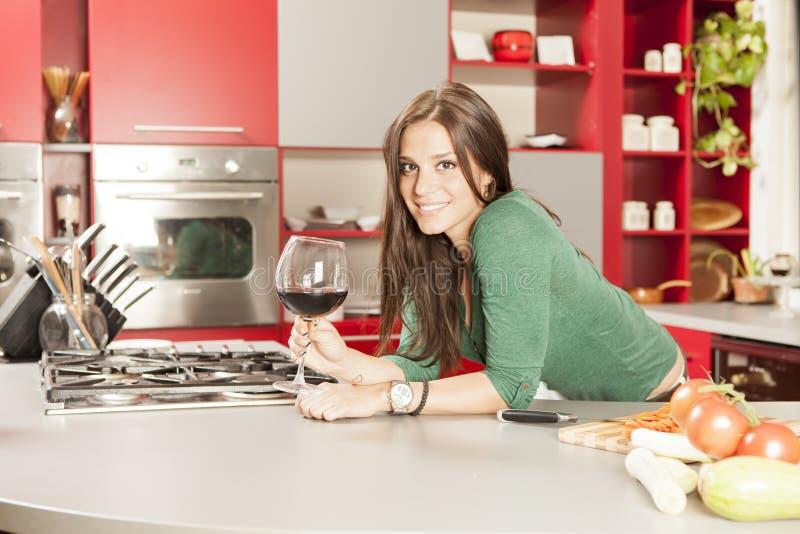 Ung kvinna i kök arkivfoton