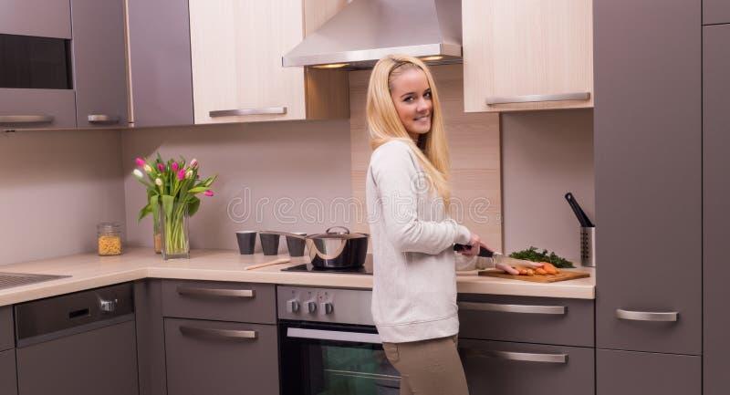 Ung kvinna i kök arkivbilder