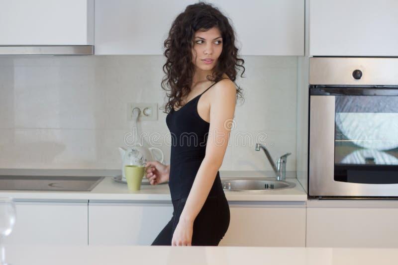 Ung kvinna i köket fotografering för bildbyråer