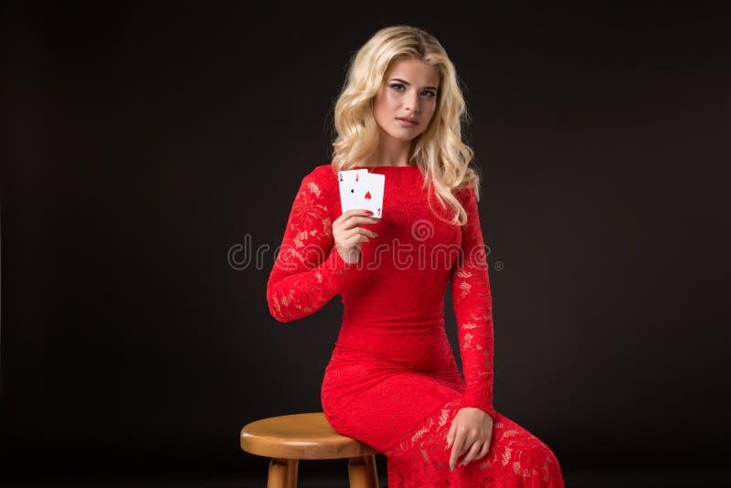 Ung kvinna i kasino med kort över svart bakgrund poker royaltyfri fotografi