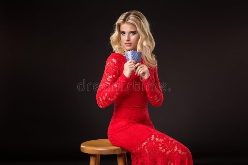 Ung kvinna i kasino med kort över svart bakgrund poker royaltyfri foto