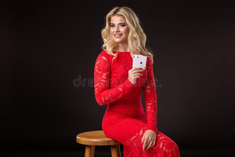 Ung kvinna i kasino med kort över svart bakgrund poker royaltyfri bild