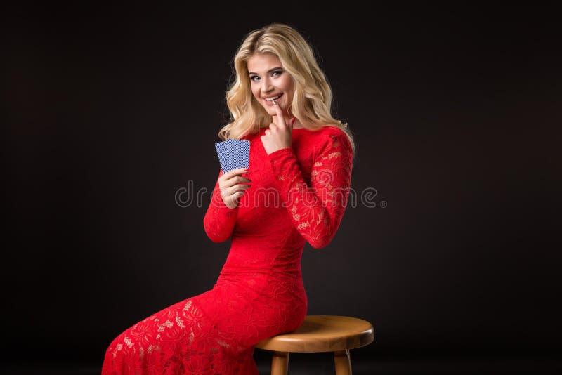 Ung kvinna i kasino med kort över svart bakgrund poker royaltyfria bilder