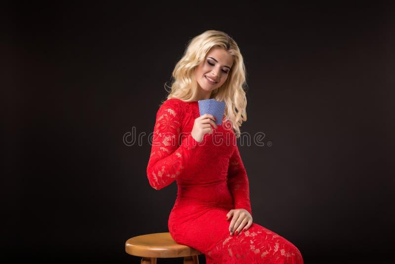 Ung kvinna i kasino med kort över svart bakgrund poker arkivfoton