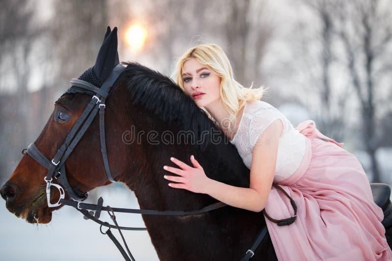 Ung kvinna i klänningridninghäst på vinterfält arkivfoton