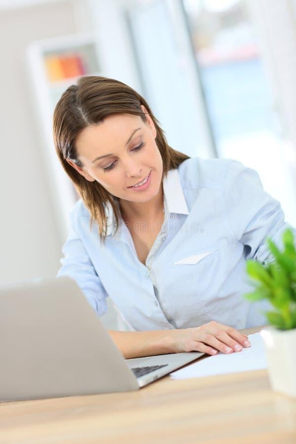 Ung kvinna i kontoret som ner skriver anmärkningar royaltyfri fotografi
