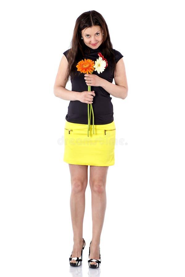 Ung kvinna i kort gul kjol med gerberas, full kropp som framåtriktat vippar på hennes huvud royaltyfri bild