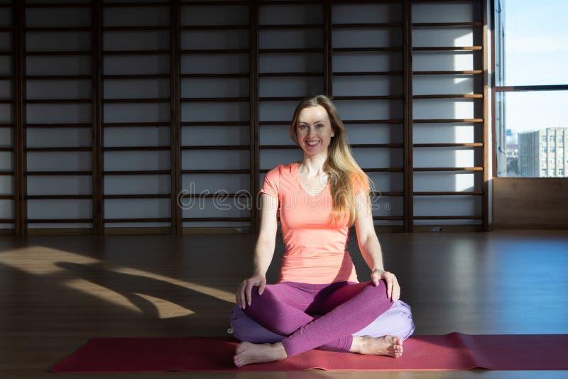 Ung kvinna i lotusblommapositionen, medan meditera royaltyfria bilder