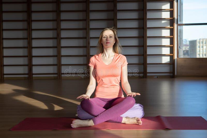 Ung kvinna i lotusblommapositionen, medan meditera royaltyfri foto