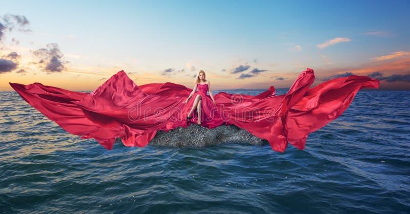 Ung kvinna i lyxig lång röd klänning royaltyfri fotografi