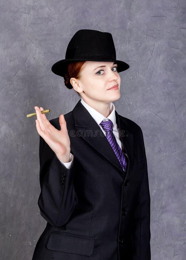 Ung kvinna i manlig stil med den mini- cigarren på grå bakgrund, flicka i dräkt och band för man` s, den vita skjortan och hatten royaltyfri foto