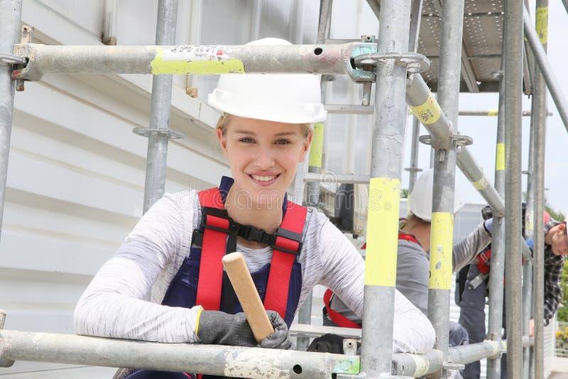 Ung kvinna i material till byggnadsställningyrkesutbildning arkivfoton