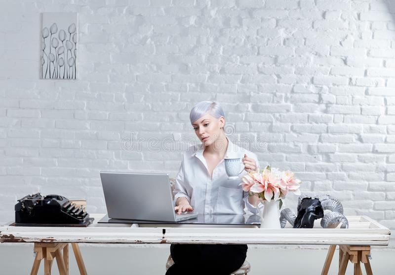 Ung kvinna i moderiktigt kontor royaltyfria foton