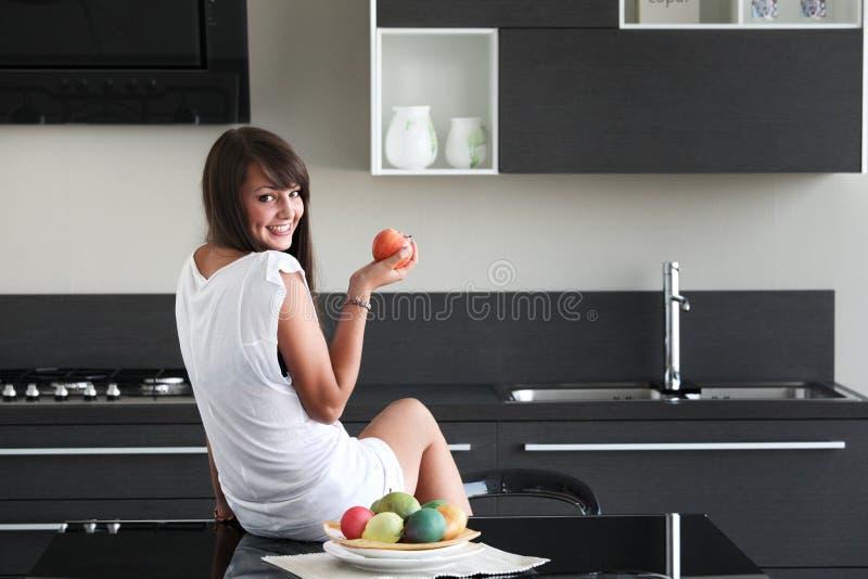 Ung kvinna i modernt kök royaltyfria bilder