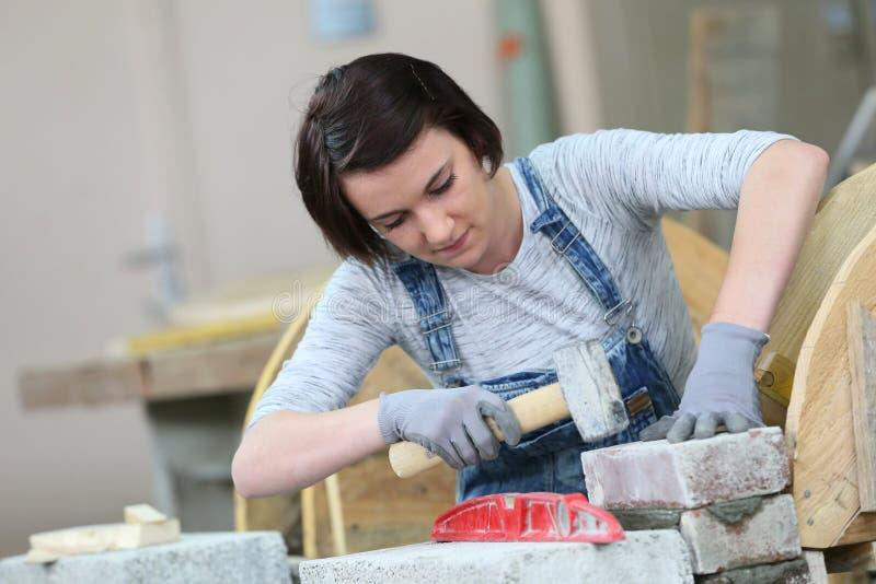 Ung kvinna i murverkskola royaltyfri bild
