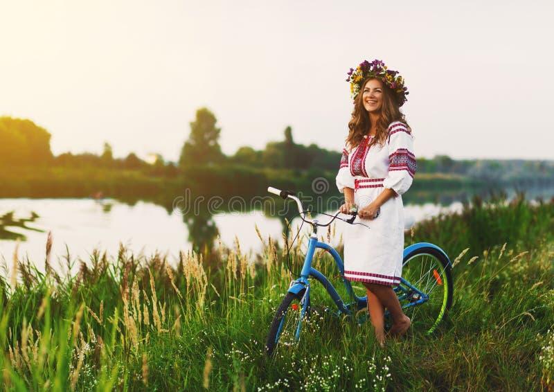 Ung kvinna i nationell ukrainsk folkdräkt med cykeln royaltyfri bild
