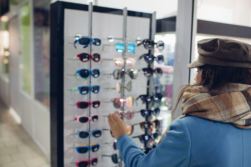Ung kvinna i optiskt lager - den härliga flickan väljer exponeringsglas i optiker shoppar royaltyfria bilder