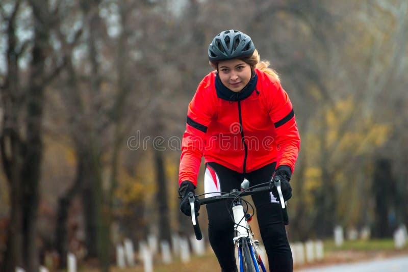 Ung kvinna i orange cykel för omslagsridningväg i parkera i den kalla Autumn Day Sund livsstil royaltyfria foton