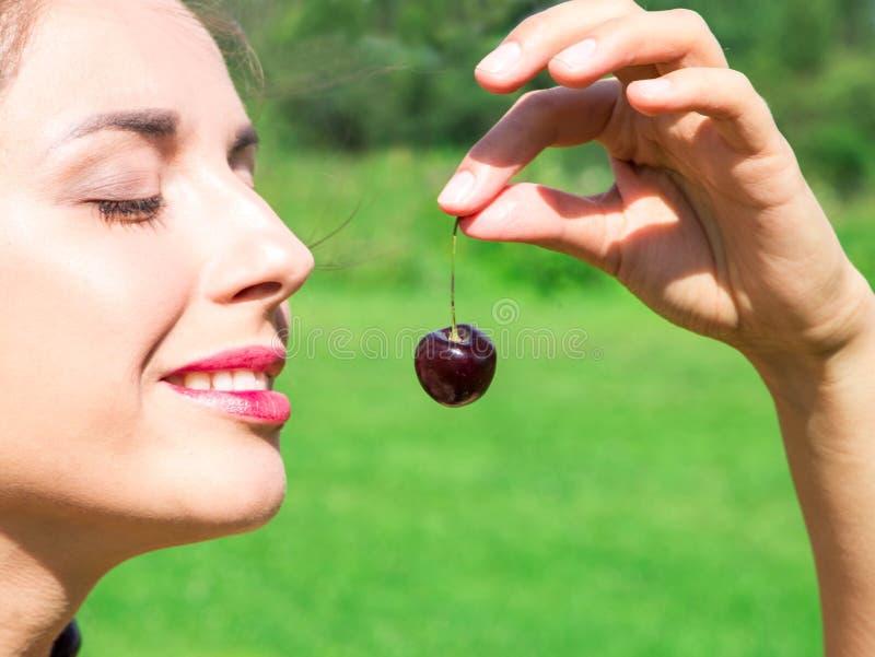 Ung kvinna i pärlor som göras av den nya körsbärsröda hållande körsbäret på öppen mun med bakgrund för sommargräsplanskog arkivbild