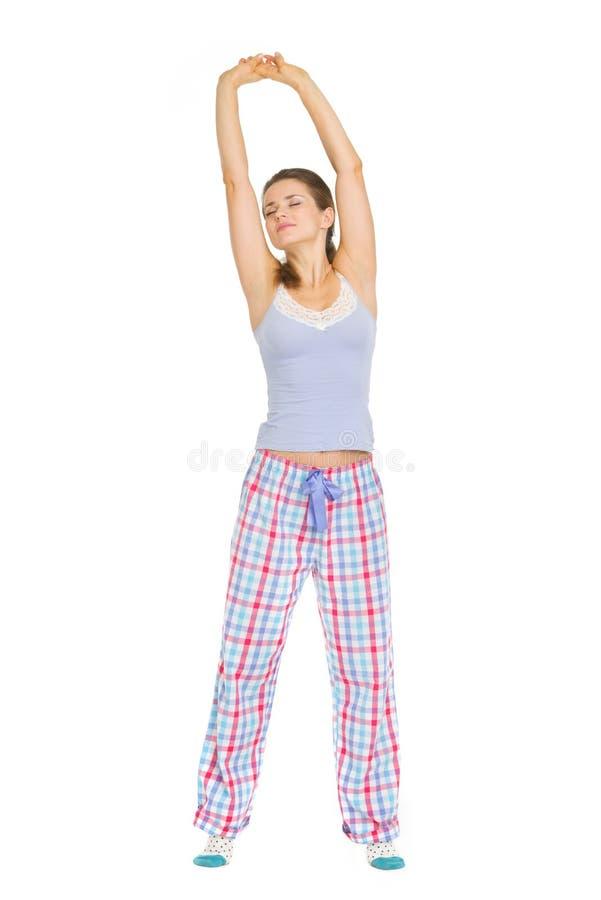 Ung kvinna i pajamas som sträcker efter sömn royaltyfri foto