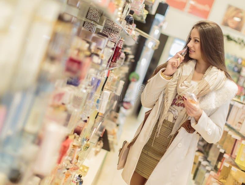 Ung kvinna i parfymeriaffär royaltyfri fotografi