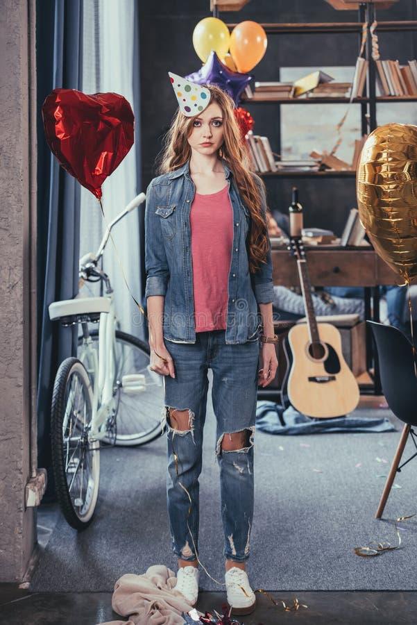 Ung kvinna i partihattanseende i smutsigt rum efter parti arkivbilder