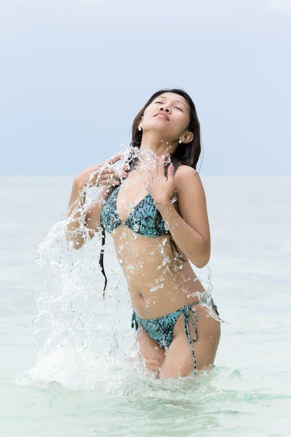 Ung kvinna i plaska för bikini arkivbild