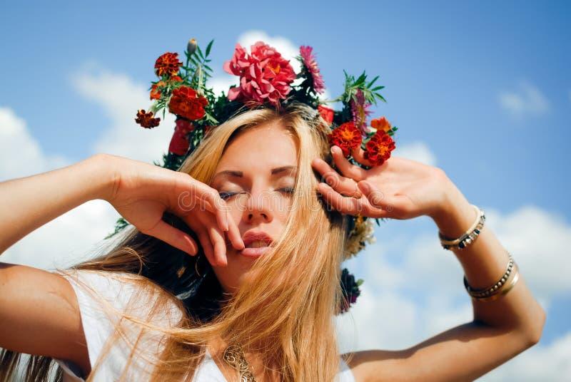 Ung kvinna i röd blommakrans med stängda ögon arkivbilder