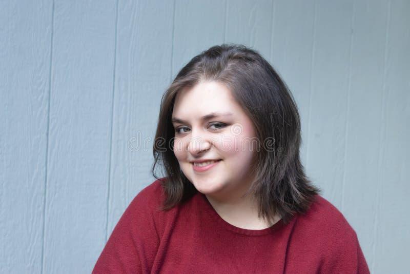 Ung kvinna i röda bästa leenden mot blått hus royaltyfri foto