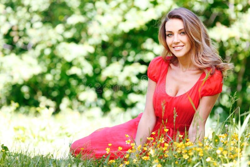 Ung kvinna i rött klänningsammanträde på gräs royaltyfri bild