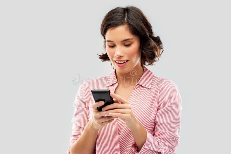 Ung kvinna i randig skjorta genom att använda smartphonen arkivfoto