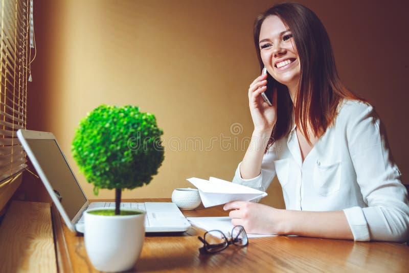 Ung kvinna i regeringsställning som talar på telefonen Ta ett avbrottsbegrepp royaltyfri fotografi