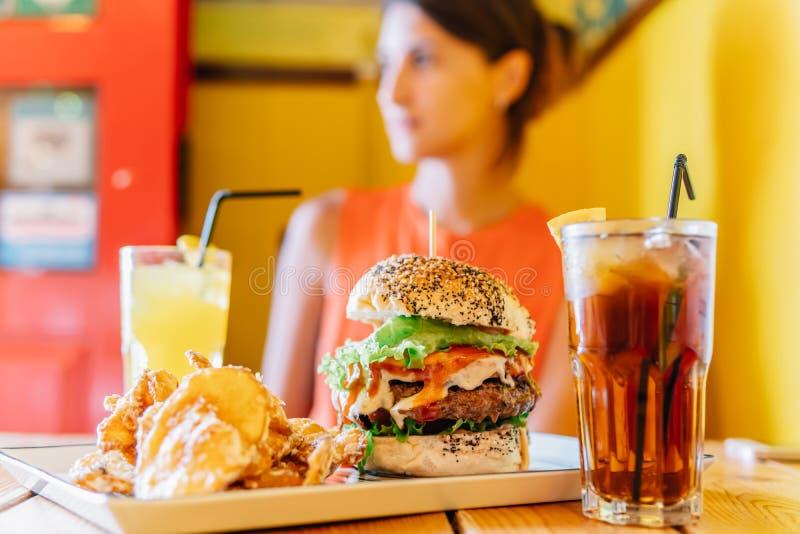 Ung kvinna i restaurang som tycker om den smakliga saftiga amerikanska nötkötthamburgaremenyn med grönsallat-, ketchup- och potat arkivfoto