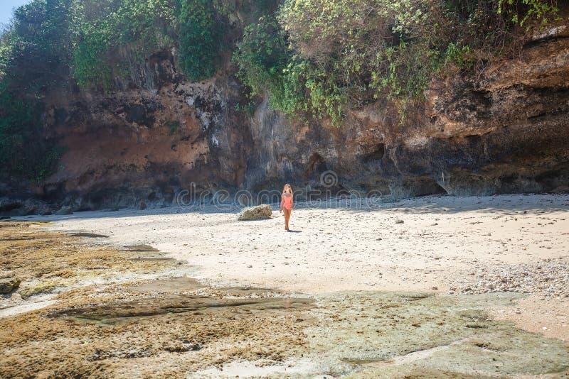 Ung kvinna i rosa baddräkt som går på den tropiska stranden arkivbilder