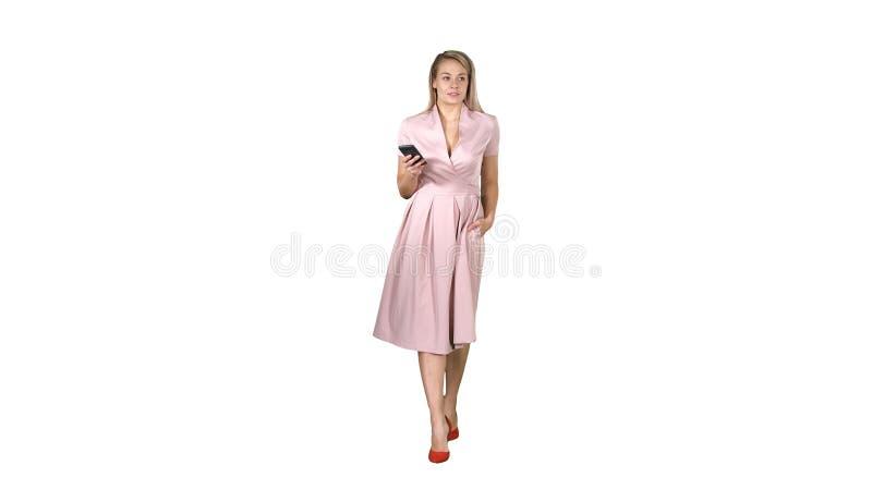 Ung kvinna, i rosa seende mobil smartphone och att smsa något, medan gå på vit bakgrund arkivbild