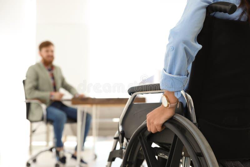 Ung kvinna i rullstol med kollegan på kontoret fotografering för bildbyråer